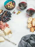 Red wine and snack set over grey background, copy space Royalty Free Stock Photo