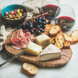 Red wine and snack variety on wooden board Royalty Free Stock Photos