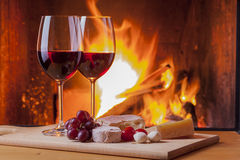 Red wine with snacks and grapes at fireplace Stock Image