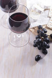 Red wine and snacks on white table. Red wine, cheese and grapes on white table Stock Images