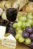 Red wine with some grapes,cheese and bread. Royalty Free Stock Photos