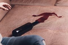 Red wine spilled on a brown couch sofa. dark bottle of red wine dropped. Red wine spilled on a brown couch sofa dark bottle of red wine dropped royalty free stock photos