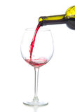 Red wine splash being poured into a wine glass. Isolated on a white background Royalty Free Stock Image