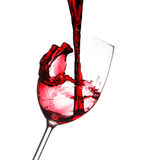 Red wine splashing in a glass, isolated on white Stock Images