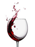 Red wine splashing. Glass of splashing red wine on white royalty free stock photos