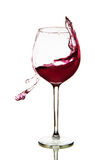 Red wine splashing in glass on a white background. Red wine glass on a white background Royalty Free Stock Images