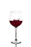 Red wine splashing in glass on a white background. Red wine glass on a white background Stock Photography