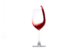 Red wine splashing out of a wineglass Royalty Free Stock Photos