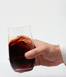 Red wine in stemless glass. In hand isolated on white background. Closeup of stemless wine glass. Test wine stock photo