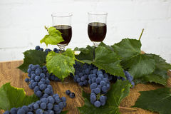 Red wine in stemware standing on the wooden background with grapes and green leaves. Stock Image
