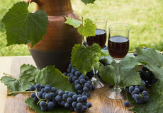 Red wine in stemware standing on the wooden background with grapes and green leaves. Stock Images