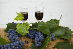 Red wine in stemware standing on the wooden background with grapes and green leaves. Royalty Free Stock Photo
