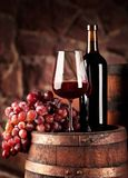 Red wine.Still life with glass and bottle of red wine, grapes and barrel.Selective focus.Wine cellar atmosphere.Copy space.  royalty free stock image
