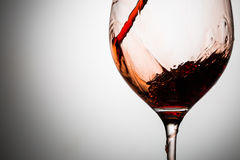 Red wine stream is poured into glass Stock Photos