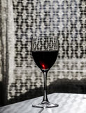Red wine on the table. Red wine in a glass  on the table by the window Royalty Free Stock Photography