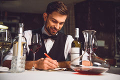 This red wine tastes well. Sommelier is sitting near table and compose wine list Stock Image