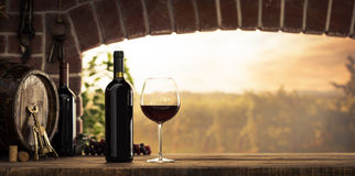 Red wine tasting in the cellar. Red wine tasting in the wine cellar: wineglass and bottles next to the window and panoramic view of vineyards at sunset stock photos