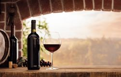 Red wine tasting in the cellar. Red wine tasting in the wine cellar: wineglass and bottles next to the window and panoramic view of vineyards at sunset Royalty Free Stock Images