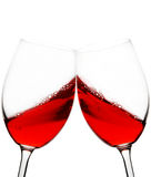 Red wine toast. Two red wine glasses raised in a toast isolated on white stock photo