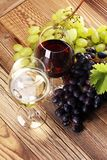Red Wine and white wine with grapes and glasses on rustic backgr. Ound Royalty Free Stock Photography