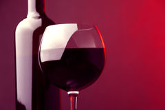 Red wine wine bottle  and wineglass red background Stock Photography