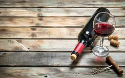 Red wine in a wine glass with a corkscrew. On a wooden background royalty free stock images