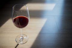Red wine in wine glass, placed on the floor with window light and shadow. Scenery and romantic concept. dramatic, scenery in the evening stock photo