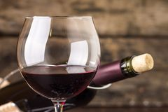 Red wine in wineglass against corked bottle. On wood background Stock Photos