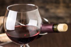 Red wine in wineglass against corked bottle. On wood background Royalty Free Stock Photo