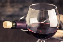 Red wine in wineglass against corked bottle. On wood background. Warm color toned image Royalty Free Stock Images