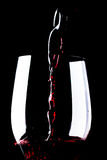 Red wine in wineglass. On a black background stock images
