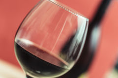 Red wine on a wineglass closeup and red background. Full wineglass close up on a red background royalty free stock image