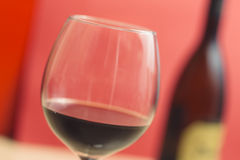 Red wine on a wineglass closeup and red background. Full wineglass close up on a red background royalty free stock photo