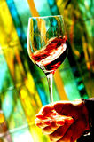 Red wine in wineglass on color background. France stock photography