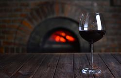 Red wine in a wineglass near the old fireplace. In a authentic restaurant royalty free stock photos