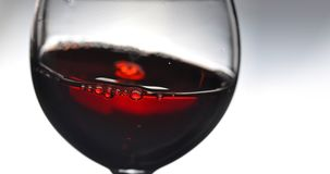 Red wine in wineglass. Red wine in wineglass on a grey background. Abstract splashing. Copy space for your text. Closeup royalty free stock photo