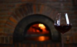 Red wine in a wineglass. Near the old fireplace in a authentic restaurant royalty free stock image