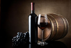 Red wine and wooden barrel. Bottle of red wine, grapes and wooden barrel Royalty Free Stock Photography