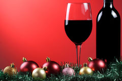 Red wine xmas. A glass of red wine and bottle with xmas decorations on a graduated red background stock photos