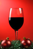 Red wine xmas. A glass of red wine with xmas decorations on a graduated red background royalty free stock images