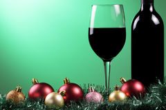 Red wine xmas. A glass of red wine and bottle with xmas decorations on a graduated green background stock image