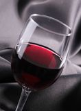 Red wineglass on silk Stock Images