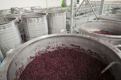 Red winegrapes in open fermenters. Red winegrapes fermenting in stainless steel open fermenters in modern winery in Australia stock photos