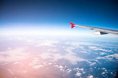 Red wing air plane fly over blue clear sky and fog above ground Royalty Free Stock Photos