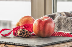 Red winter apples with cinnamon sticks Royalty Free Stock Photos