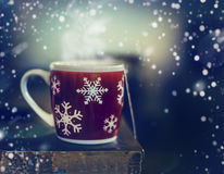Red winter snowflakes cup with hot tea drink on rustic table with snow Stock Images