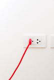 Red wire with flat pin plugged into socket Stock Photo
