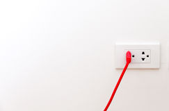 Red wire with flat pin plugged into socket Royalty Free Stock Images