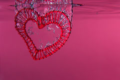 Red Wire Heart Falling into Water Stock Photography