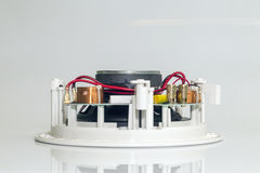 Red wires and golden clips on a white loudspeaker. Close view stock image